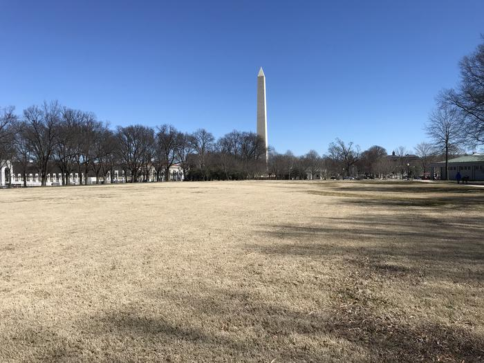 The photo shows an open grassy field flanked by trees. The Washington Monument and World War II Memorial can be seen in the background.Field M10