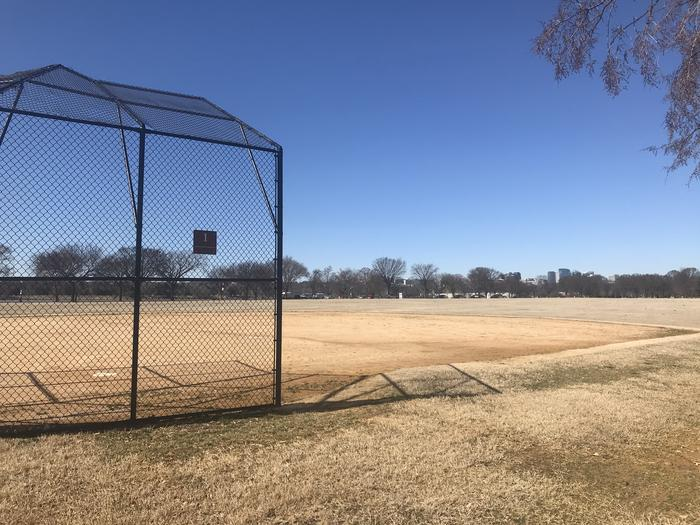 The photo shows a softball field with a backstop, infield, and grassy outfield. There are scattered trees in the background.Field S1