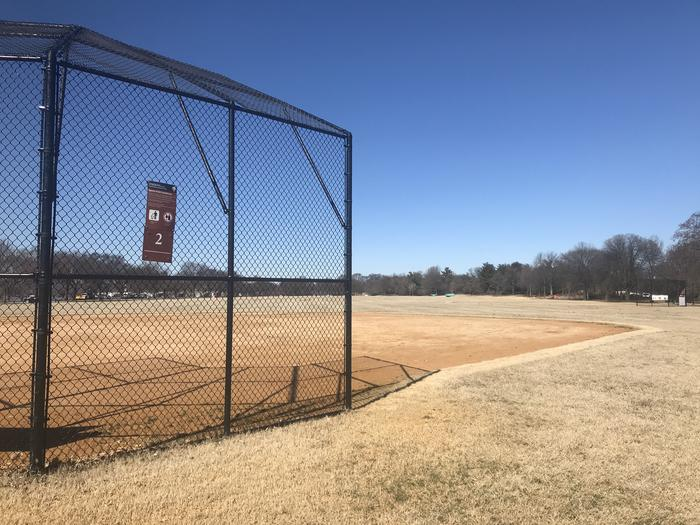 The photo shows a softball field with a backstop, infield, and grassy outfield. There are scattered trees in the background.Field S2