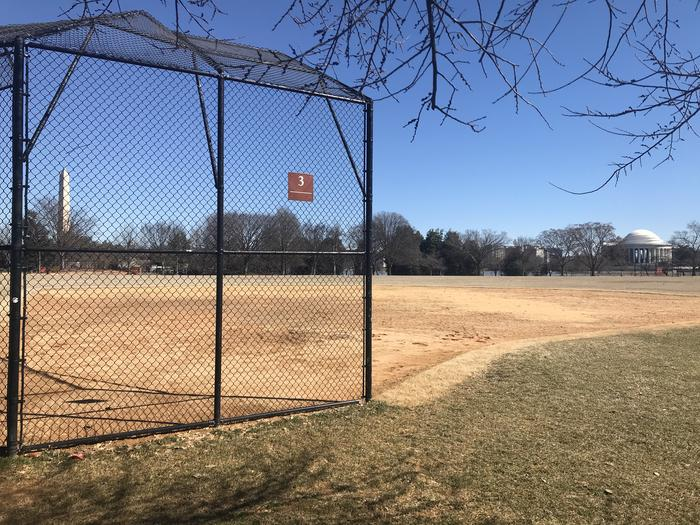 The photo shows a softball field with a backstop, infield, and grassy outfield. The Washington Monument, Thomas Jefferson Memorial, and scattered trees are visible in the background.Field S3