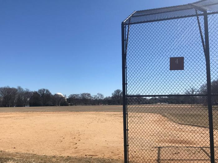 The photo shows a softball field with a backstop, infield, and grassy outfield. The Thomas Jefferson Memorial and scattered trees are visible in the background.Field S4