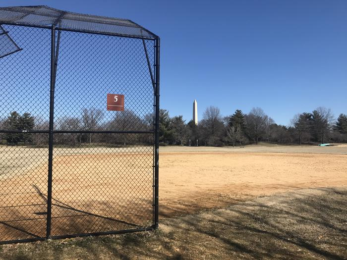 The photo shows a softball field with a backstop, infield, and grassy outfield. The Washington Monument and scattered trees are visible in the background.Field S5