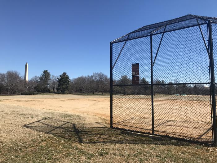 The photo shows a softball field with a backstop, infield, and grassy outfield. The Washington Monument and scattered trees are visible in the background.Field S6