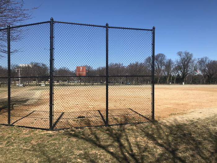 The photo shows a softball field with a backstop, infield, and grassy outfield. The Lincoln Memorial and scattered trees are visible in the background.Field S7