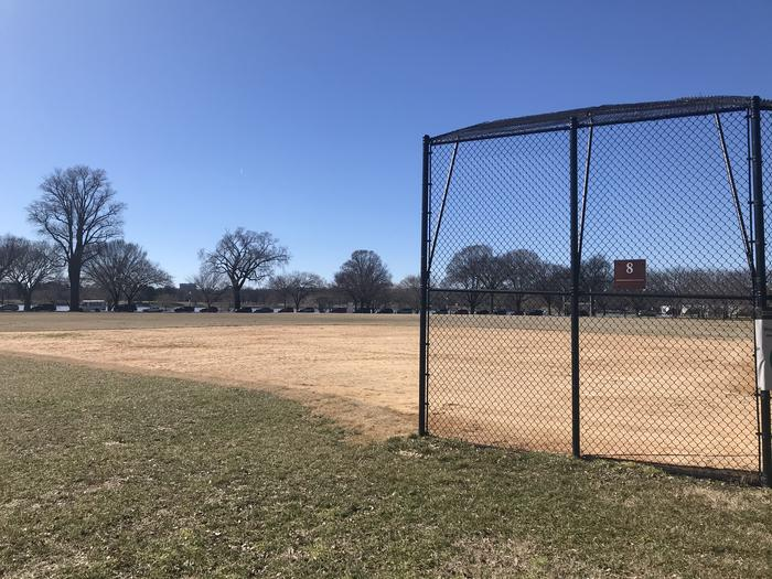 The photo shows a softball field with a backstop, infield, and grassy outfield. Scattered trees are visible in the background.Field S8