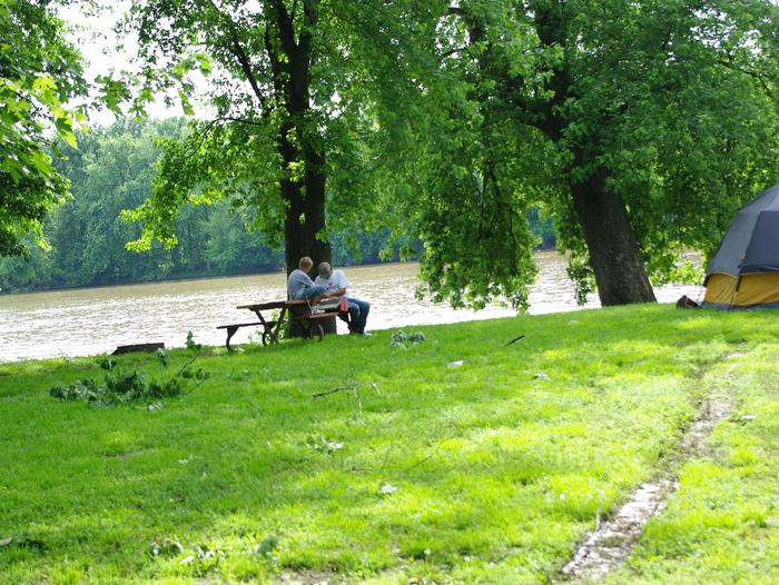 Father/Son on table along river with tent