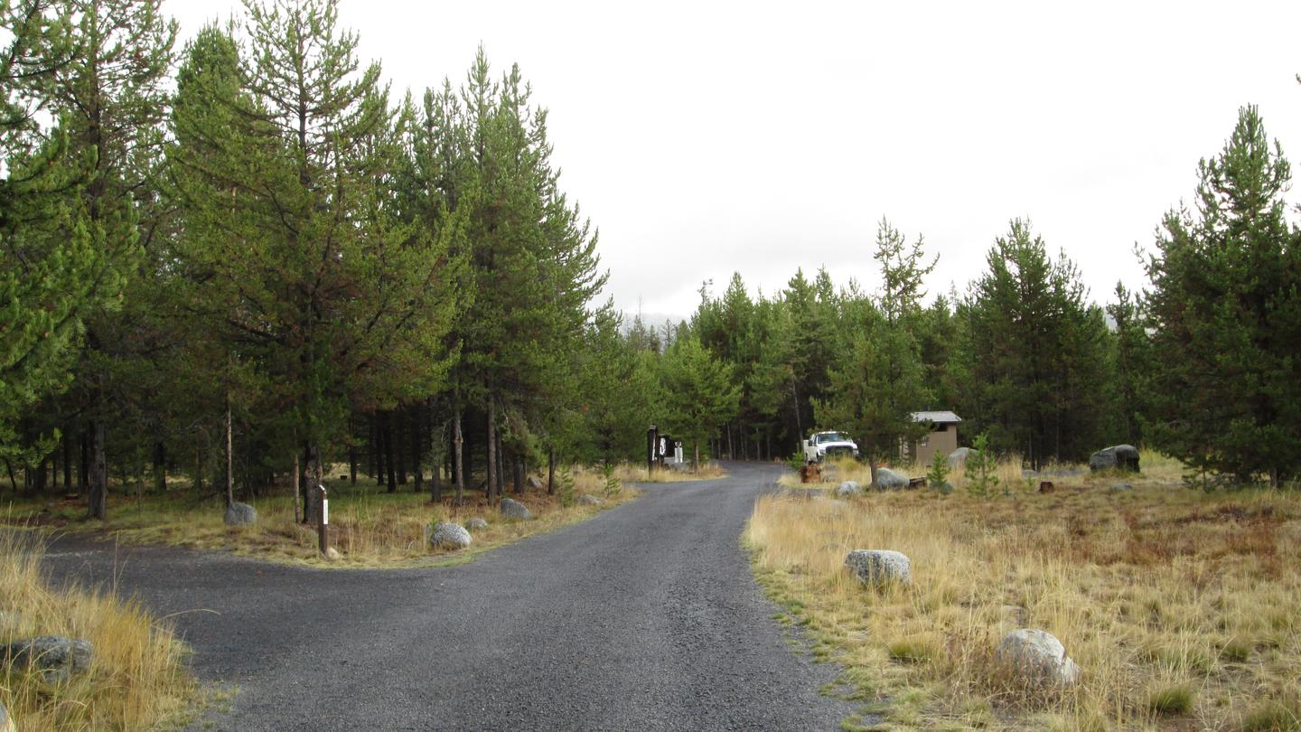 View of east part of campground including gravel road, campsite, toilet, fee station and white truckEast portion of NFJD Campground