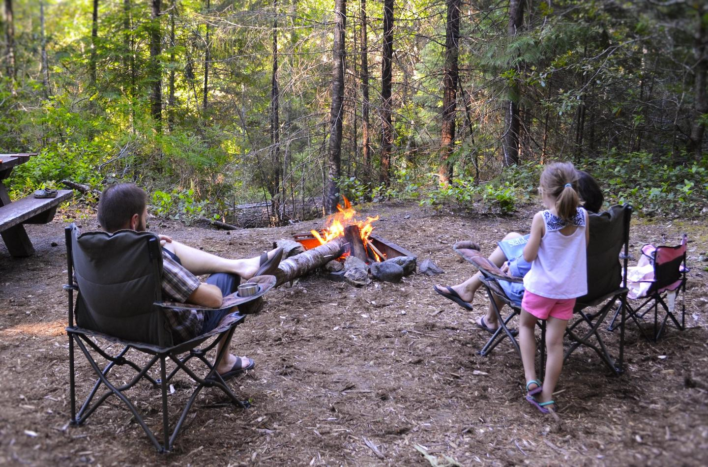 Family enjoying Cave Creek CampgroundFamily sitting around a campfire at Cave Creek Campground