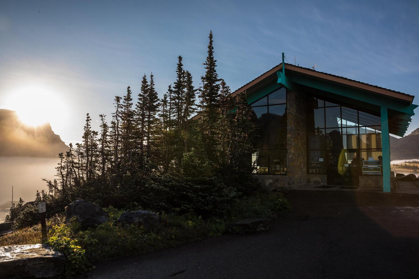 Logan Pass Visitor Center at SunriseThe Logan Pass Visitor Center at sunrise on a late summer morning. The visitor center has large windows and is surrounded by small alpine trees.