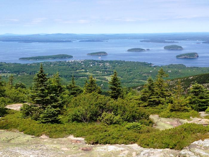 Sweeping view from Cadillac Mountain across a forested slope and island-spotted bay to distance hills.View of Frenchman Bay and the Porcupine islands from Cadillac Mountain.