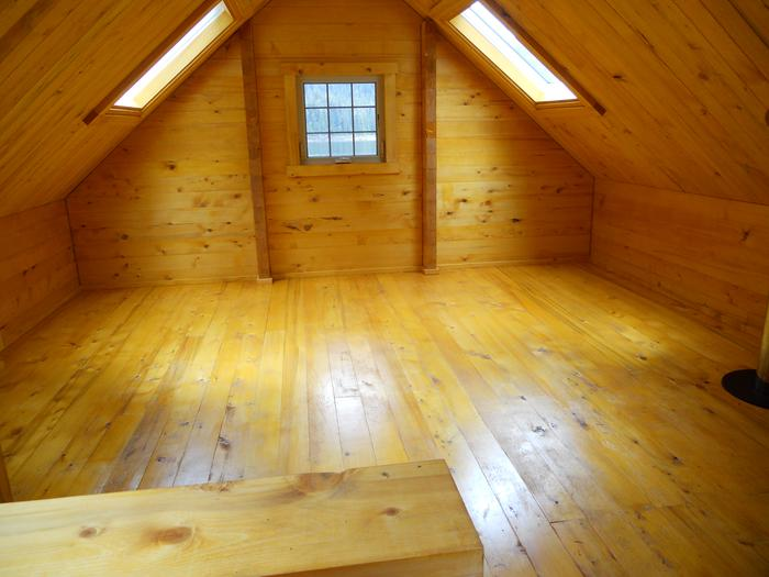 View of the loft inside the cabin with windows.Cabin loft area