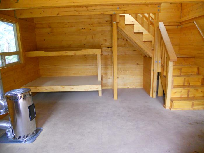 Inside of cabin showing oil stove, bunkbed, staircase.Interior of cabin