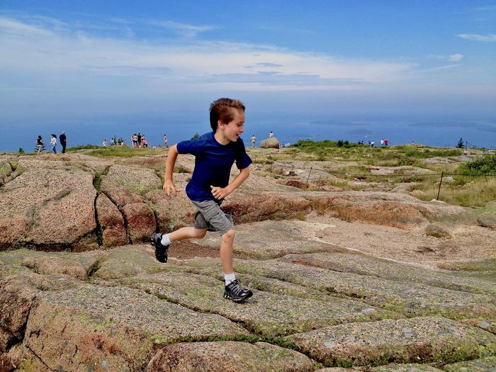 Young boy running across granite rock on Cadillac Mountain with view of bay in background.Enjoying the open summit of Cadillac Mountain.