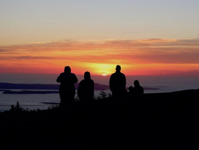 Five people shown in silhouette watch the bright orange and red sunrise on the horizon overlooking the ocean from Cadillac Mountain.Sunrise on Cadillac Mountain.