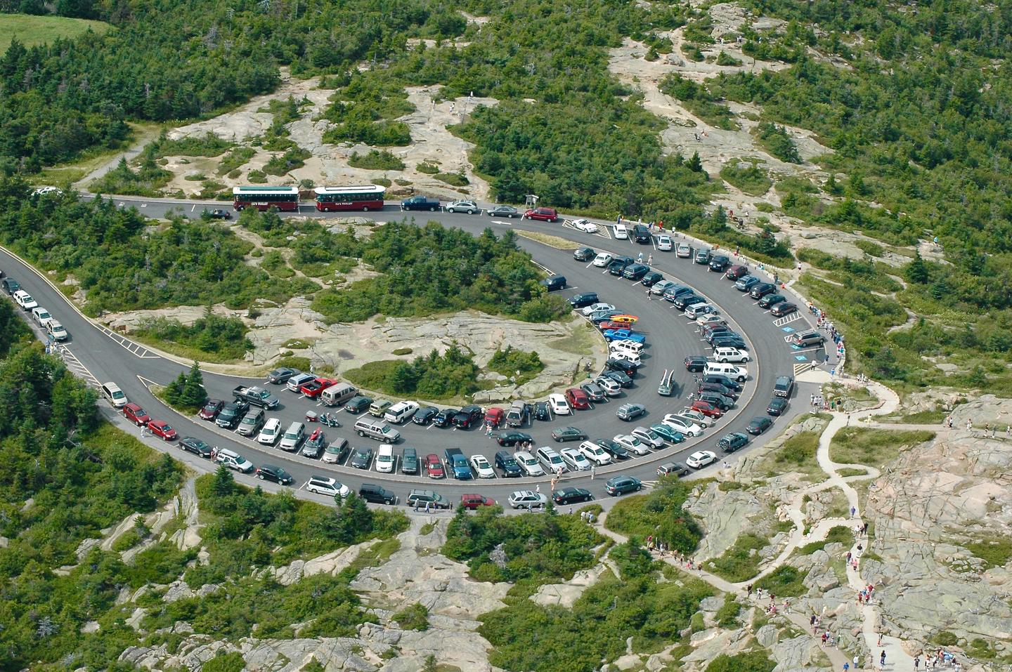 Aerial view of the Cadillac Summit parking area full with cars and two trollies surrounded by trees and granite ledges.Bird's eye view of the Cadillac Summit parking area and paved walks.