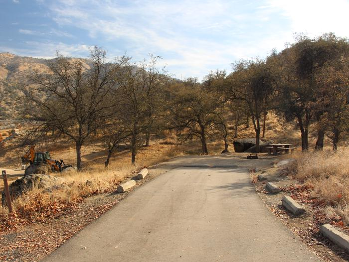 Somewhat shaded site with table and grill. Site limited on tent capacity. Flat driveway with site in the rear.