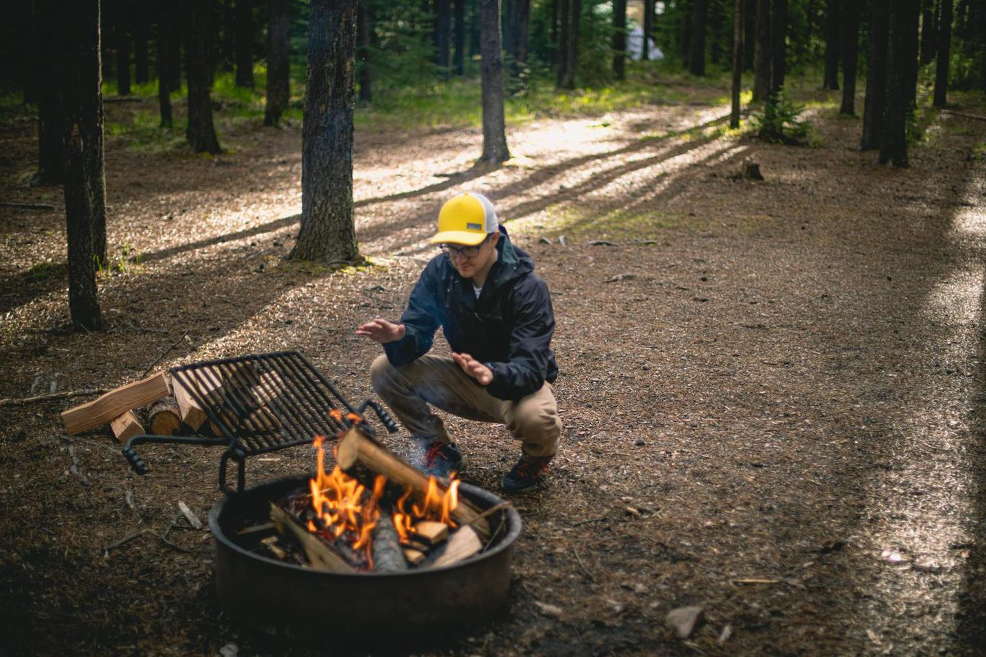 Campfire at Bowman Lake CampgroundA camper wearing a bright hat warms their hands while squatting near a campfire in a forest clearing.