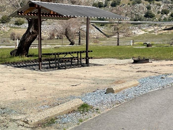 Campsite pad at site 20.Shade shelter, picnic table, and fire ring. Located near a large rock.