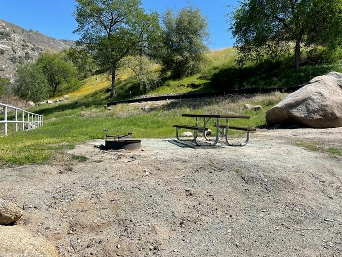 Campsite pad in the spring. There is a retaining wall hand rail  and some rocks on the site. The site is open, no trees on the site. Picnic table and fire ring above driveway for site 22. The site has a step up into the site. There is no shade on the site.