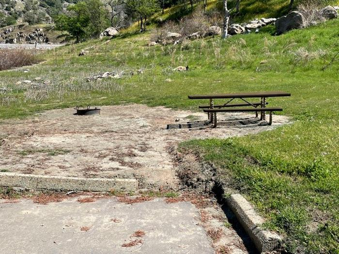 Site area for #25.Picnic table and fire ring for campsite. There is no shade. The site is behind the parking pad.