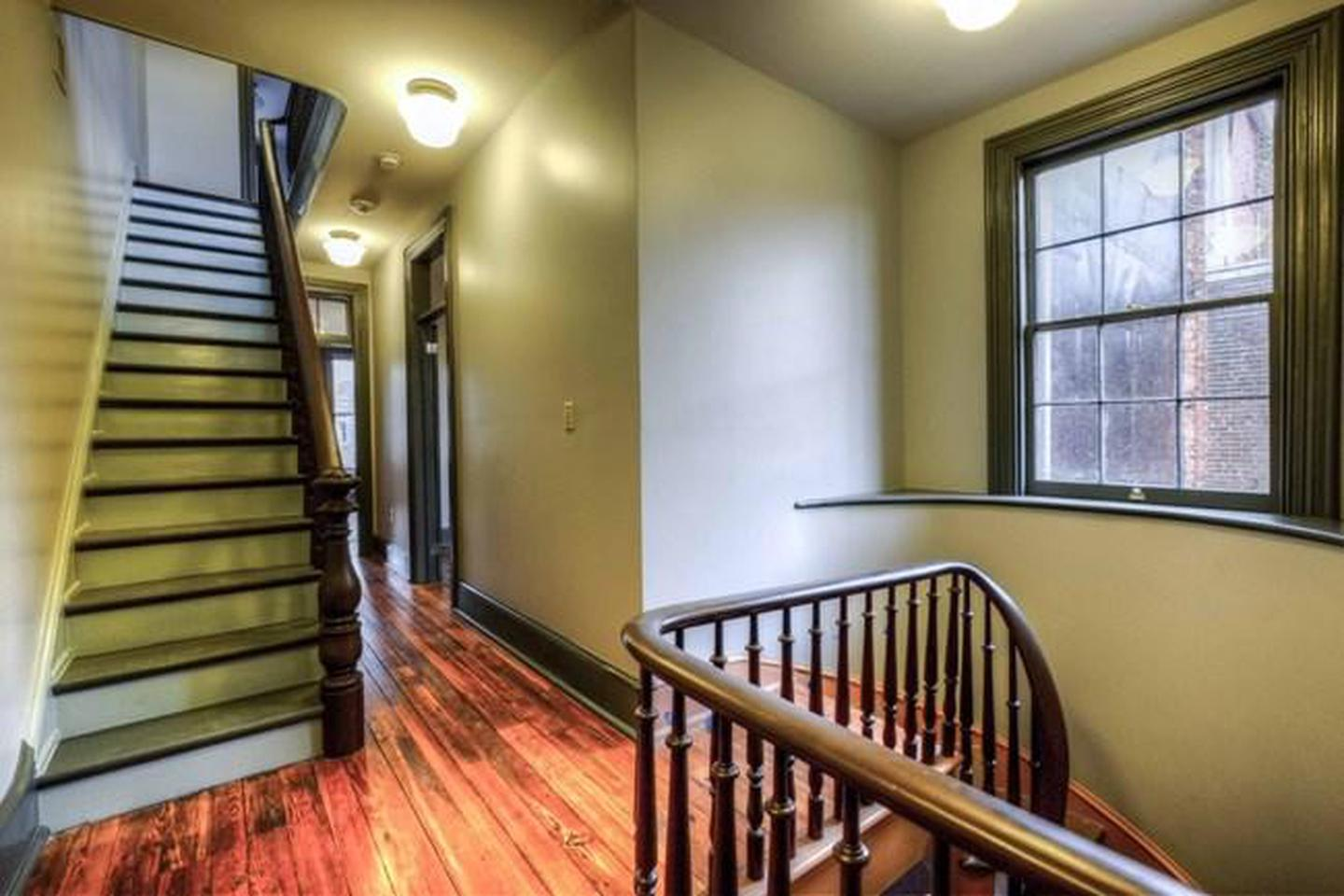 Hallway and staircases on second levelThe second floor of the Woodson Home with restored original floorboards, steps, and railings.