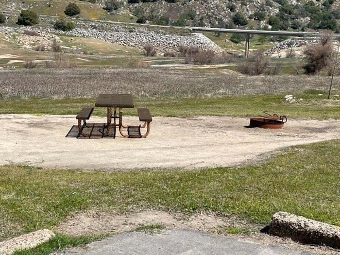 Campsite area.Picnic table and fire ring at campsite. No shade at site.