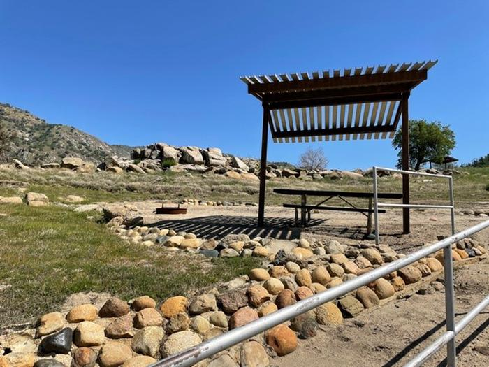Site area.Shade shelter, picnic table, and fire ring at campsite.