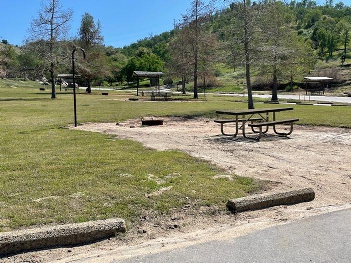 Site area. No shade for camping units.Site area includes picnic table, fire ring, and lantern hook.