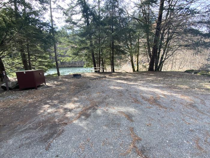 Campground containing a picnic table, campfire ring, and tent pad.View of campsite.