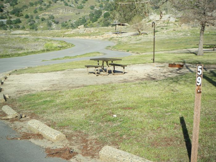 Springtime photo of campsite pad. Table, lantern hook/post, campfire ring.