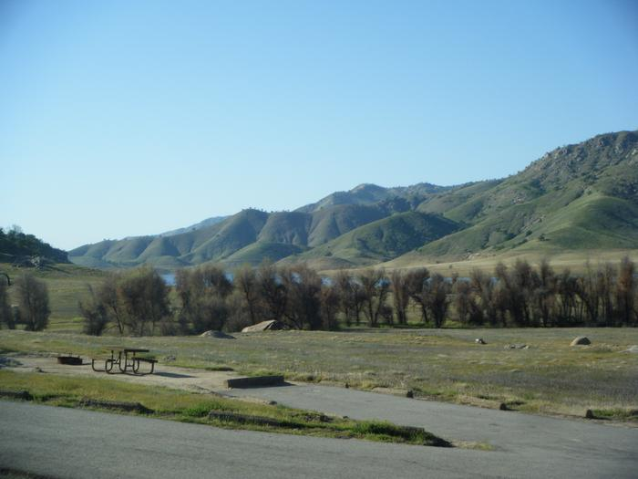 Small campsite with seasonal view of Lake Kaweah. No shade on site. Subject to flooding during high water season.Back in driveway for two units only. Small tent, family tent for 8. Camper, Pop Up, Vehicle, or small RV.