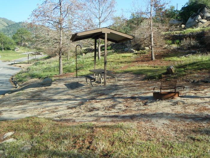 Small campsite with seasonal Lake Kaweah view. Small tent or family tent for 8. Parking line shared with campsite 67. Pull through site for two units. Campsite has table, campfire ring, lantern post/hook. Shade cover over the table only.