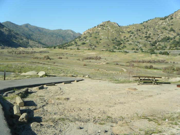 Small open campsite. Great seasonal view of Lake Kaweah. Night sky viewing is really good. Springtime view of the open campsite. There is no shade.  At the base of a hill, on the corner. Road to the campsite is one way. Small tent or family tent for 8.  Campsite has table and campfire ring.