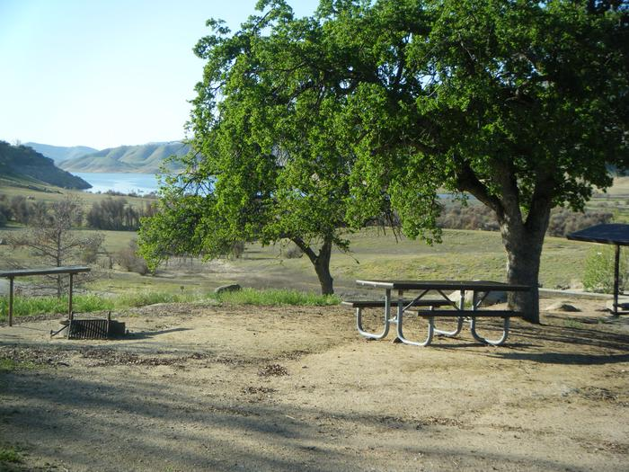 Back in campsite on a hill. Campsite has seasonal views of Lake Kaweah. Good for small tent or family tent for 8. Springtime view of the small back in campsite on the hill. Campsite has campfire ring, prep table, picnic table. Limited or no shade on campsite. Erosion is present on campsite. Close to the restroom.