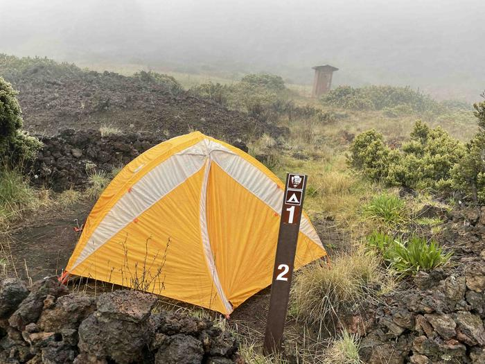 foggy setting orange tent on dirt patch outhouse in the backgroundHōlua 1 Tent Site