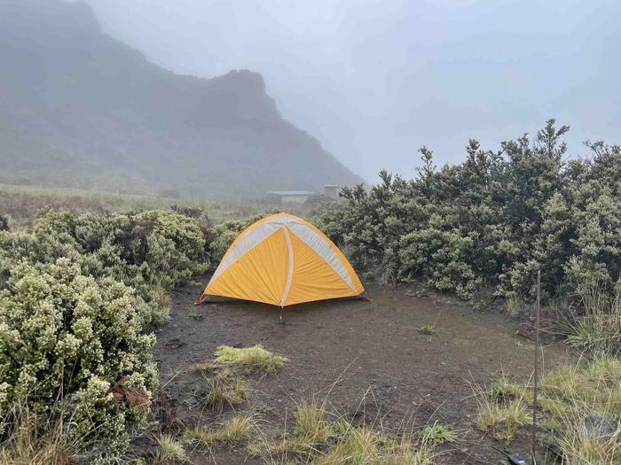 orange tent in dirt patch with cliff outlineHōlua tent site 3 with tent and view of pit toilet