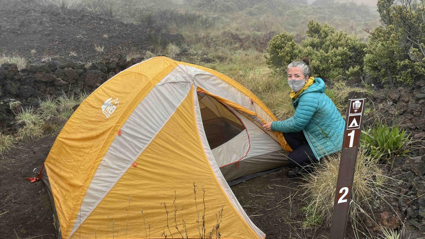Camper sets up tentCampers enjoy the cool weather in the Haleakalā crater at Hōlua Campground