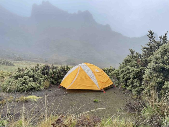 orange tent in dirt patch with foggy cliffConditions at Hōlua campground can vary from sunny and warm to misty and cool quickly!