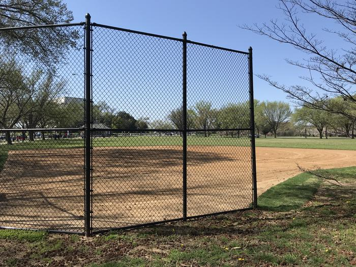 The image shows field S11, with a backstop and infield in the foreground, and a grassy outfield, scattered trees, and the Lincoln Memorial visible in the background.Field S11