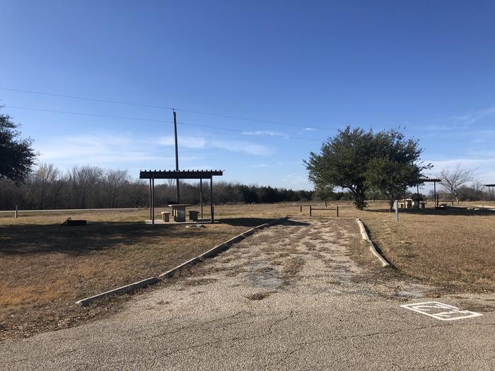 Site 12 has a metal rooftop shelter and picnic table, water and electric hook ups, and a grill and fire pit. It has room for a standard size camper and small vehicle.Site 12 has a metal rooftop shelter and picnic table, water and electric hook ups, and a grill and fire pit. It has room for a standard size camper and small vehicle