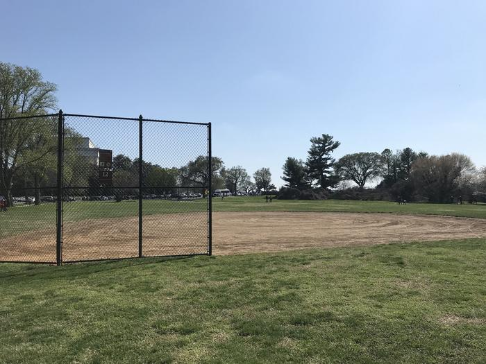 The image shows field S12 with a backstop and infield in the foreground, and a grassy outfield, scattered trees, and the Lincoln Memorial visible in the background.Field S12
