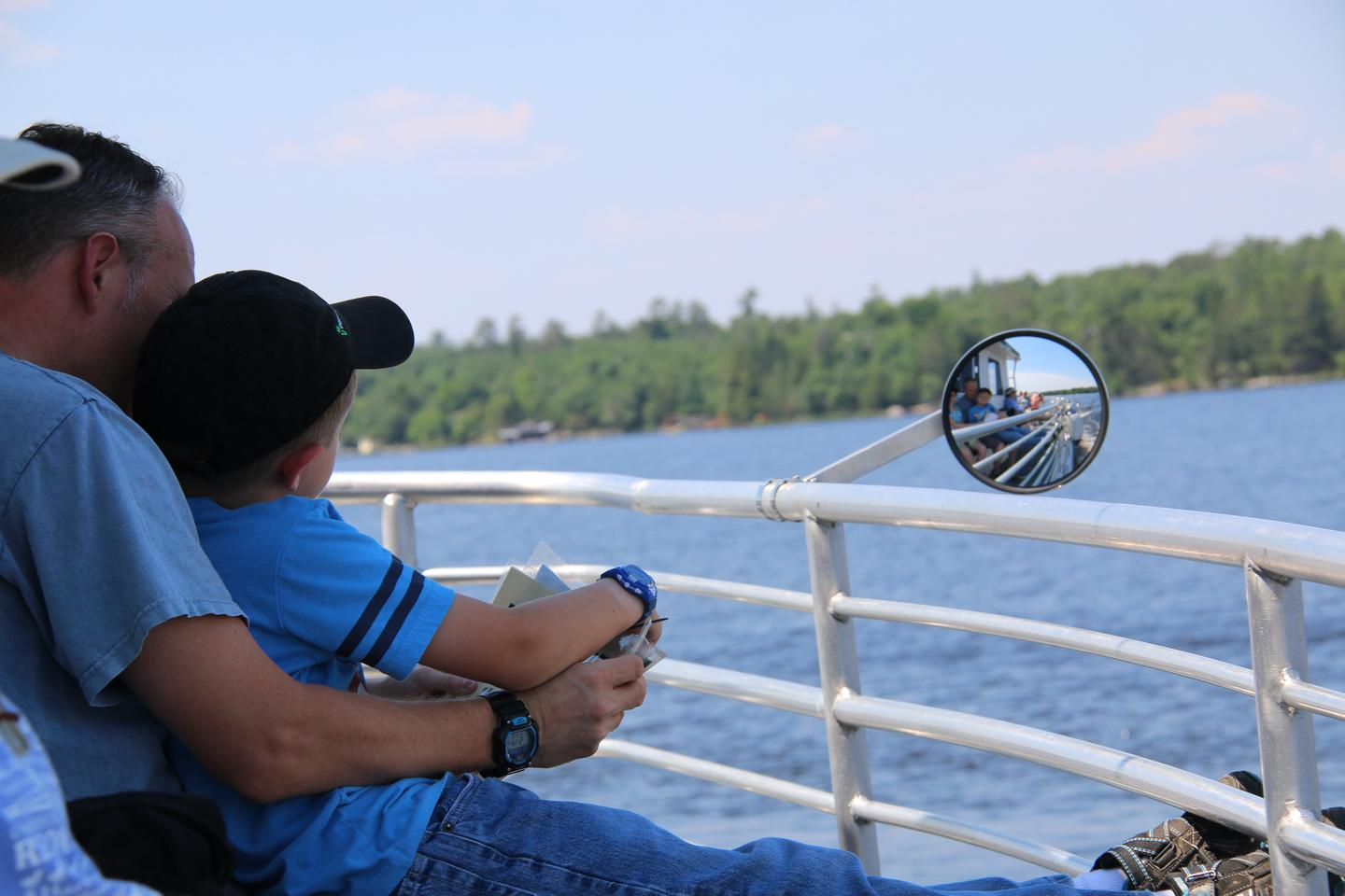 Visitors taking in the view from the Voyageur Tour BoatFather and son enjoying the view from atop the Voyageur tour boat