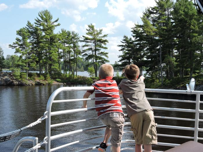 Voyageurs National Park boat toursTwo boys sightseeing from the railings of the Voyageur tour boat