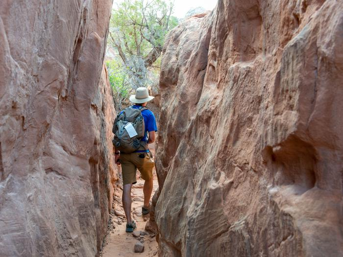 Hiker in a narrow slot canyon in the Fiery Furnace A hiker passes through a narrow passageway in the Fiery Furnace area of Arches National Park