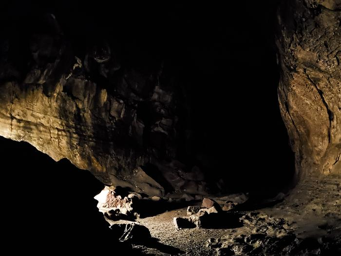 A picture of the rocky cave floor and walls illuminated by lantern in Ape Cave.Without a light source Ape Cave is completely dark, some 60 feet underground. Here, a hiker has illuminated a junction while entering Upper Cave, with their lantern.