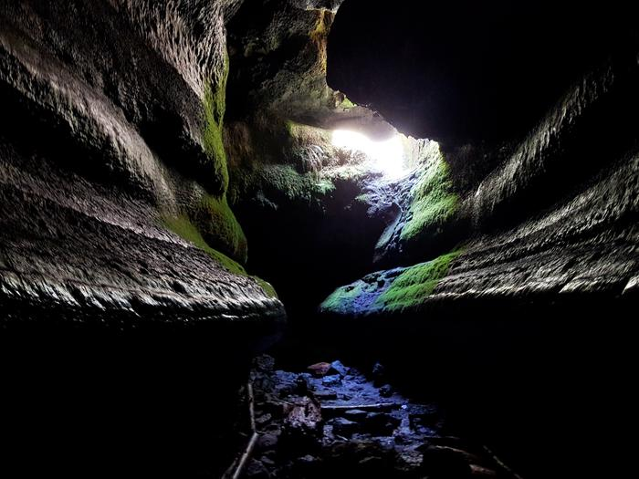 A small hole in the ceiling of Ape Cave, known as the Skylight, illuminates the dark cave walls below.