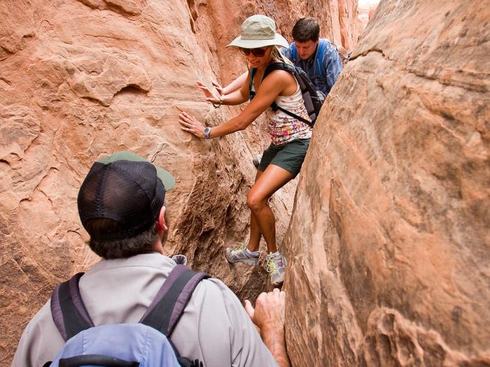 Visitors navigating a narrow passage in the Fiery Furnace.