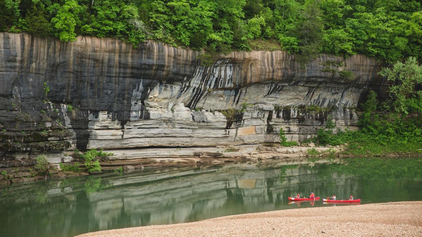 Painted Bluff at Buffalo Point CampgroundTwo red canoes paddle by Painted Bluff on the Buffalo River.