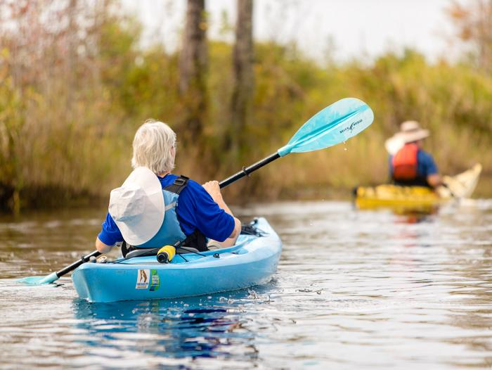 Kayaker in a blue kayak with a black and blue paddle. Second kayaker in background in a yellow kayak, wearing an orange life jacket and a brown hat.Paddling Down the Suwannee Canal