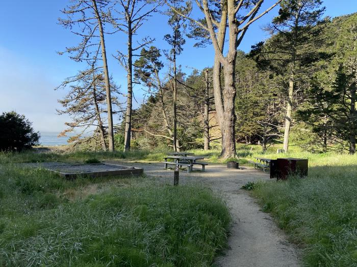 A campsite with a raised tent platform, a food storage bin and several picnic tables arranged around a fire ring from a distance.Site 2 from a distance.